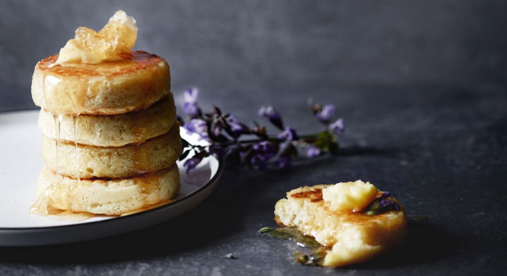 Homemade crumpets dripping with honey butter