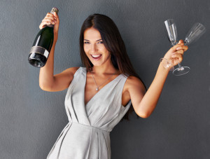 Portrait of a gorgeous brunette holding champagne and two flutes
